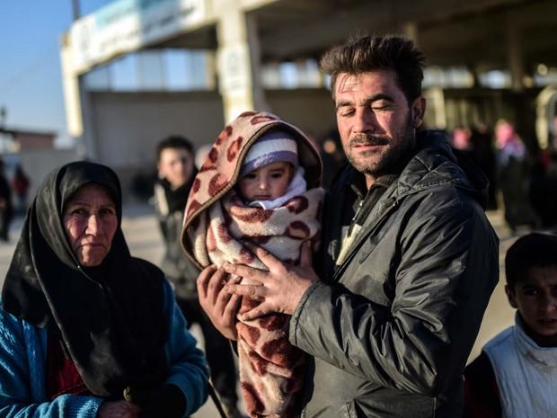 Homem segura seu bebê nesta sexta-feira (5) na fronteira da Síria com a Turquia (Foto: BULENT KILIC / AFP)