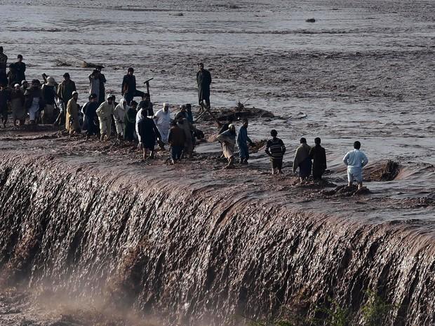Paquistaneses atravessam uma rua inundada após fortes chuvas na periferia de Peshawar. Pelo menos 53 pessoas morreram e 60 ficaram feridas com deslizamentos de terra e queda de telhados no noroeste do Paquistão e as áreas da Caxemira (Foto: A Majeed/AFP)