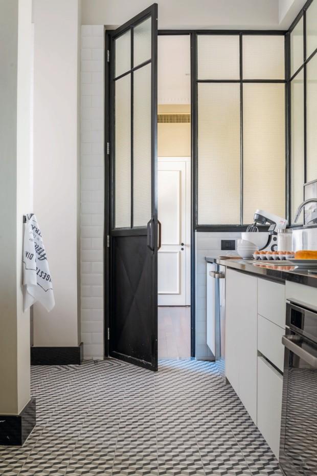 Cozinha. Tem estilo industrial moderno, com porta de aço pintada de preto e vidros aramados, piso de ladrilho hidráulico e armários da Florense em tom cinza (Foto: Sambacine)