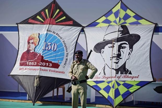 Policial é visto em meio às figuras que fazem homenagens ao líder espiritual hindu Swami Vivekanand (à esq.) e o revolucionário Bhagat Singh (Foto: Ajit Solanki/AP)