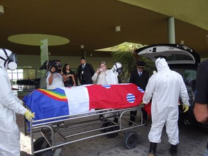 Usando roupas especiais, técnicos do cemitério para colocam corpo no carro (Foto: Katherine Coutinho/G1)