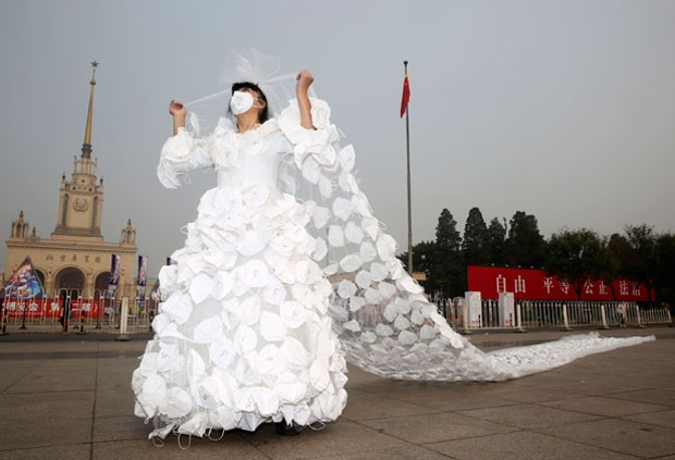 Kong Ning criou vestido de noiva decorado com centenas de máscaras contra a poluição (Foto: AP)