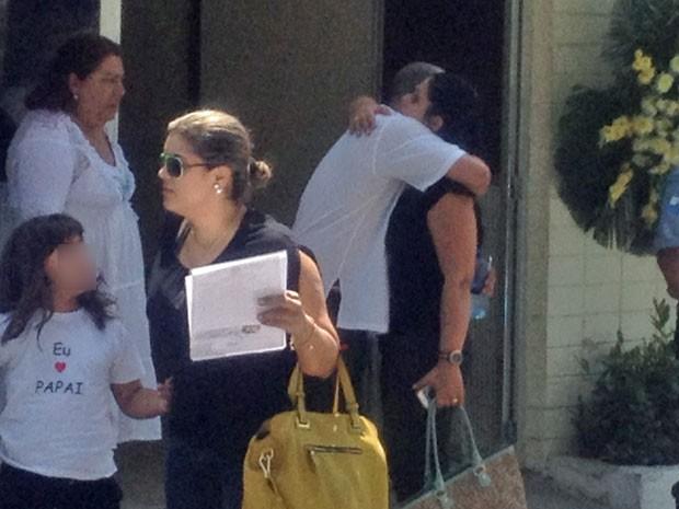 Filha usa camisa em homenagem ao pai; ao fundo a viúva é consolada (Foto: Henrique Coelho / G1)