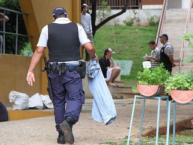 PM leva calça para homem que andava nu pela região central de Brasília; no fundo, ele aparece sentado, conversando com outro policial (Foto: Vianey Bentes/TV Globo)