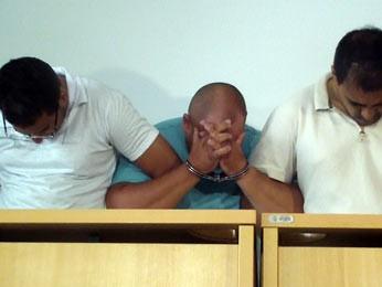 Na delegacia, apenas um dos supeitos conversou com jornalistas. O funcionário do BRB (à direita, de camisa branca) negou participação nos crimes (Foto: Ricardo Moreira / G1)