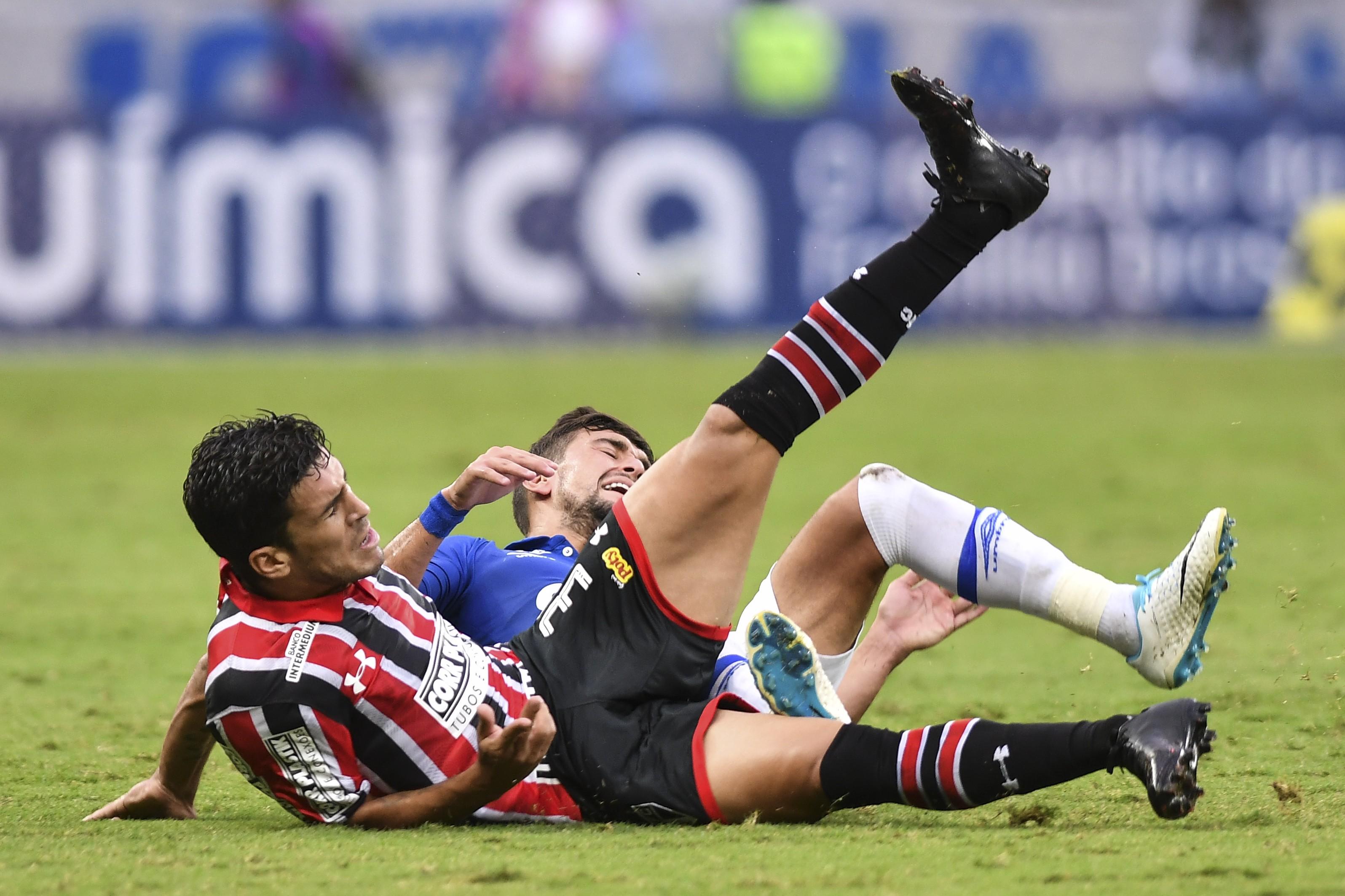 Marcinho, do São Paulo, e Arrascaeta, do Cruzeiro, se trombam e caem durante partida da primeira rodada do Campeonato Brasileiro (Foto: Getty Images/ Pedro Vilela)