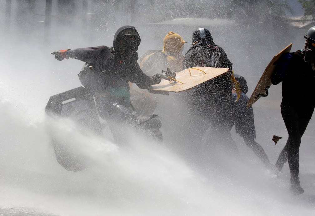 Opositores venezuelanos entram em confronto com forças de segurança durante protesto nesta quinta-feira (18) em Brasília (Foto: REUTERS/Carlos Garcia Rawlins)