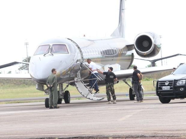 O traficante, de camiseta branca, embarcou em uma aeronave da Polícia Federal sob um forte esquema de segurança (Foto: Inaê Brandão/ G1 RR)