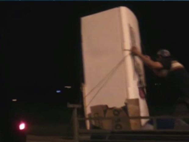 Homem segura geladeira em carretinha, na BR-153, em Goiânia, Goiás (Foto: Reprodução/ TV Anhanguera)
