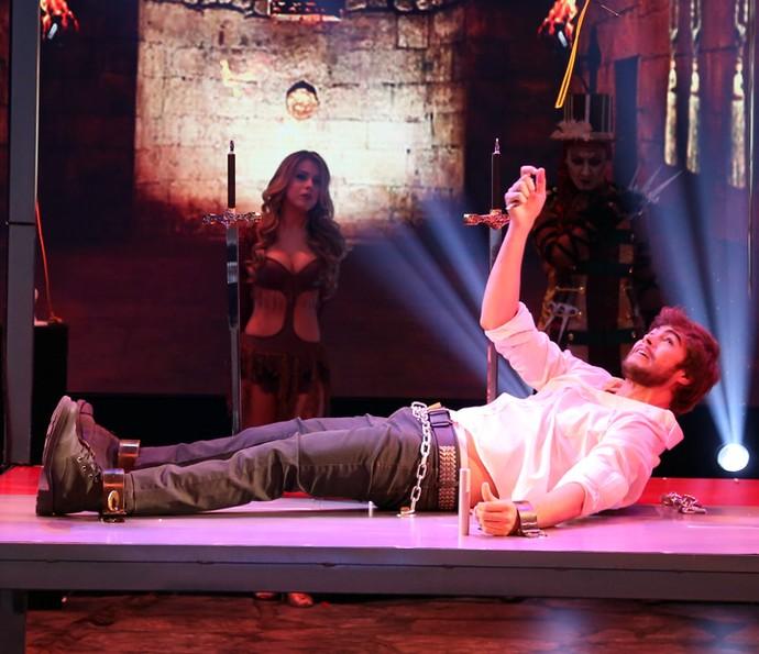 Rafael Vitti tenta se desvencilhar das correntes no palco do 'Domingão' (Foto: Carol Caminha / Gshow)