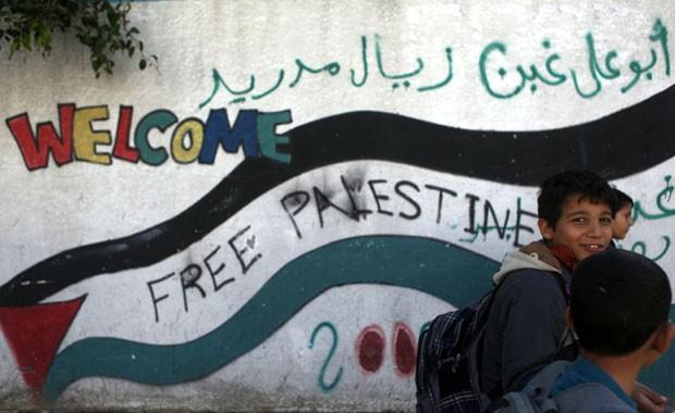Meninos palestinos passam em frente a mural na cidade de Gaza nesta quarta-feira (28)  (Foto: Patrick Baz/AFP)