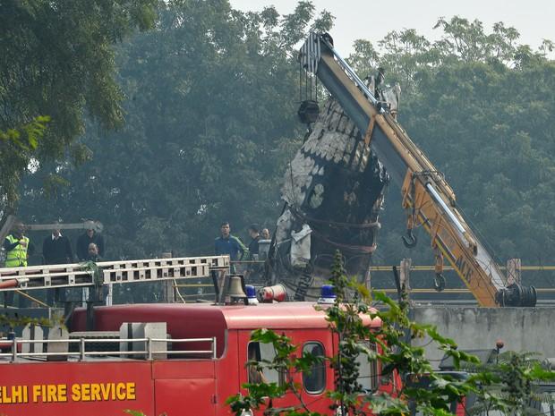 Destroços de avião acidentado são retirados de local de acidente nos arredores de Nova Déli, na Índia, nesta terça-feira (22) (Foto: Chandan Khanna/AFP)