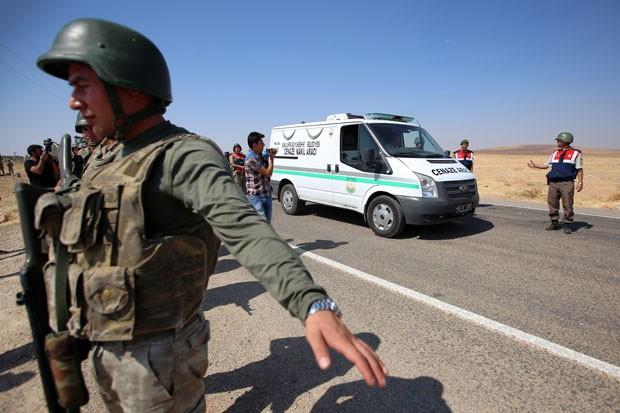 Policiais turcos fazem a segurança de comboio com os corpos das crianças sírias que morreram em um naufrágio na Turquia a caminho de seu funeral em Kobane, na Síria, nesta sexta-feira (4)  (Foto: Emrah Gurel/AP)
