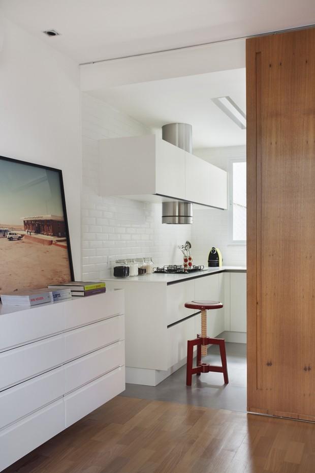 A porta retrátil de madeira freijó separa a cozinha do living quando necessário. Ela foi projetada pelo escritório InTown.  O ambiente foi revestido com cerâmica Liverpool da Portobelo. Armários da Ornare. Banco do LZ Studio. Coifa do Fast Shop (Foto: MCA Estúdio/Divulgação)