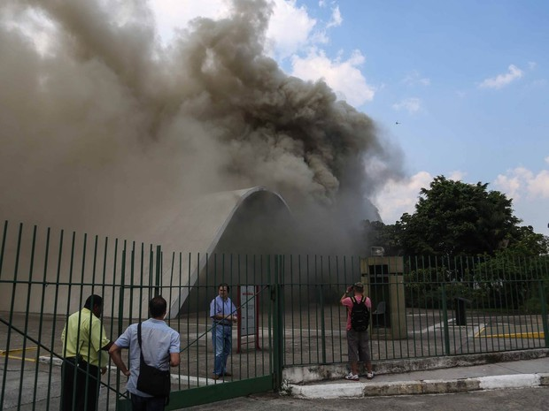 Pessoas observam a fumaça do incêndio que atinge o auditório Simon Bolívar do Memorial da América Latina, na Barra Funda, Zona Oeste de São paulo (Foto: William Volcov/Brazil Photo Press/Estadão Conteúdo)