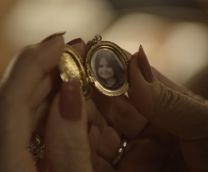 Ela sofre ao olhar para a única foto que tem da filha (Foto: TV Globo)