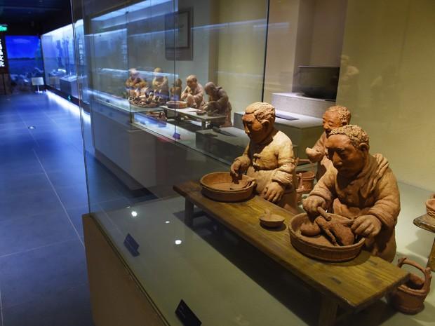 Entre as peças do museu, estão estátuas de argila mostrando a produção do famoso prato da culinária chinesa (Foto: Greg Baker/AFP)