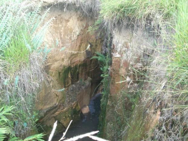 No fundo da cratera passa um esgoto, que causa mau cheiro na região, diz morador (Foto: Antônio Madureira/Arquivo Pessoal)