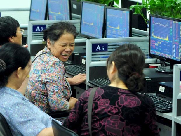 Investidoras riem em frente as telas com cotações das bolsas chinesas (Foto: Reuters)