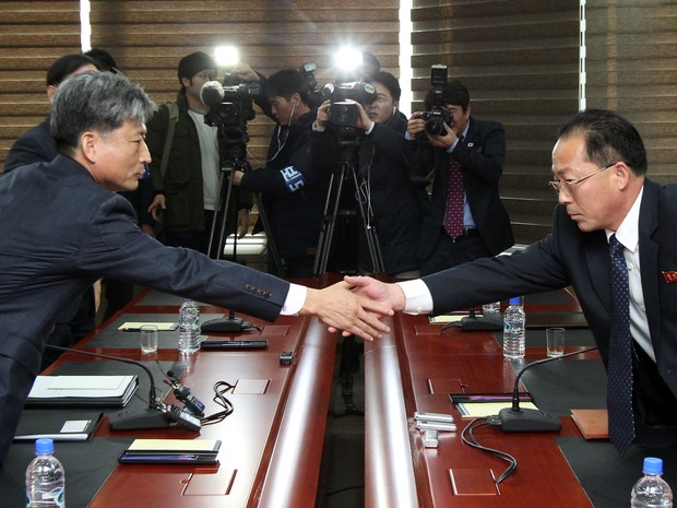 O vice-ministro da unificação da Coreia do Sul, Hwang Boo-Gi, cumprimenta seu colega norte-coreano, Jon Jong-Su, durante reunião entre os dois países na zona industrial de Kaesong nesta sexta-feira (11) (Foto: AFP)