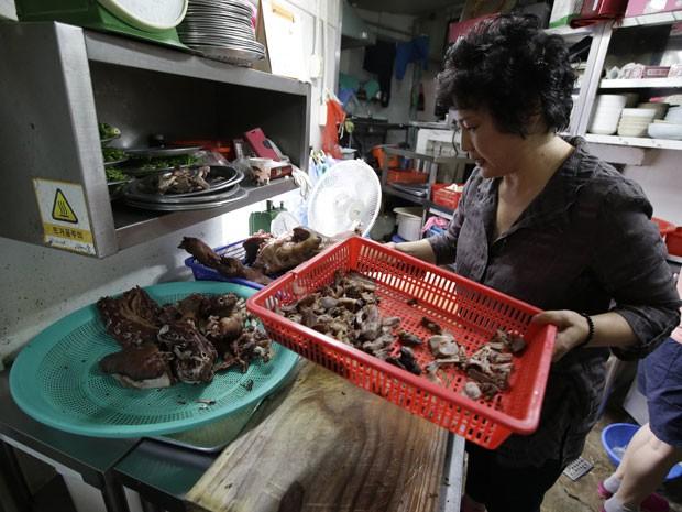A chef Oh Keum-il, dona do restaurante Daegyo, mostra como cozinhar carne de cachorro; estabelecimento que existe desde a década de 1980 vai fechar (Foto: Lee Jin-man/AP)