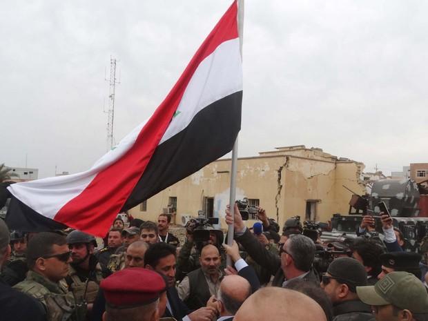 Premiê iraquiano Haider al-Abadi ergue bandeira do Iraque na cidade de Ramadi nesta terça-feira (29) (Foto: REUTERS/Stringer)