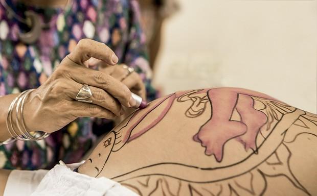 As mãos da parteira Naolí Vinaver finalizando com batom o desenho de como o bebê está dentro da barriga da mãe. (Foto: Naolí Vinaver (arquivo pessoal))