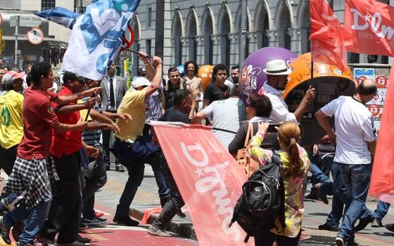 Militantes do PT e do PSDB trocam tapas, chutes e bandeiradas em briga em frente ao Teatro Municipal de São Paulo (Foto: Michel Filho/Agência O Globo)