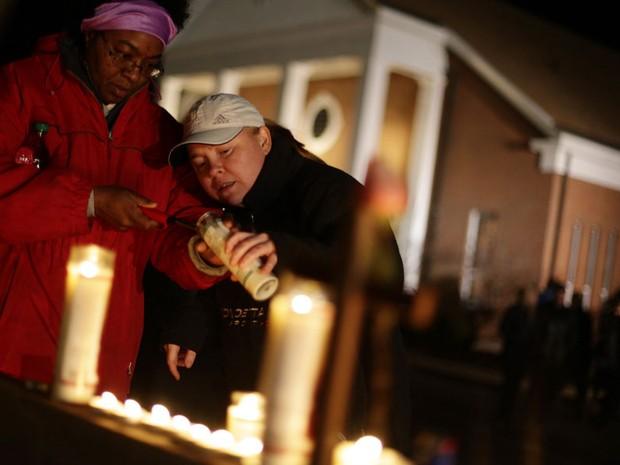 Duas mulheres acendem velas em forma de homenagem às vítimas mortas nesta sexta-feira (Foto: Joshua Lott/Reuters)