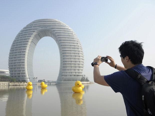 Homem fotografa o Sheraton Huzhou Hot Spring Resort, conhecido como Hotel Dônut ou Hotel Ferradura (Foto: Sean Yong/Reuters)