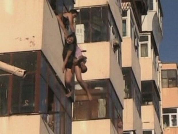 Um homem da província chinesa de Heilongjiang, que estava na varanda de sua casa, conseguiu pegar em plena queda uma mulher de 20 anos que pulou do apartamento acima, em uma aparente tentativa de suicídio. (Foto: Reuters/CCTV)
