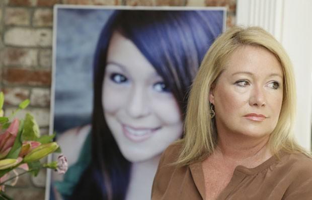 Em foto de 2013, Sheila Pott posa ao lado de uma imagem de sua filha, Andrie, que se matou após ter sido estuprada em uma festa. Dois suspeitos do crime serão julgados a partir desta quarta-feira (31) (Foto: Marcio Jose Sanche/AP)