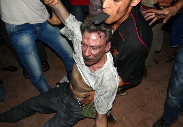 Civis líbios ajudam um homem que, segundo testemunhas, seria o diplomata americano J. Christopher Stevens, logo após o ataque em Benghazi; Stevens acabou morrendo (Foto: AFP)