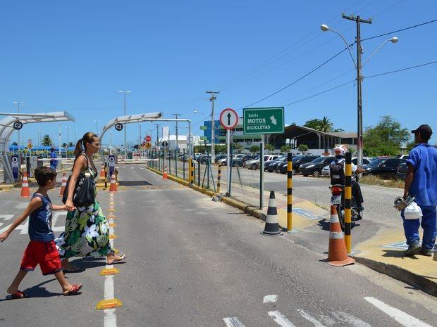 Mulher atravessa estacionamento do shopping para buscar o carro estacionado do lado de fora para evitar a cobrança da taxa (Foto: Marina Fontenele/G1 SE)