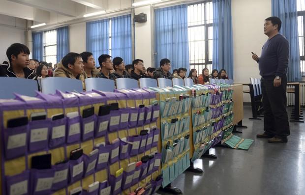 Na Universidade Normal de Hebei, aparelhos ficam na primeira fileira e virados para o professor, armazenados em bolsos especiais (Foto: AP)