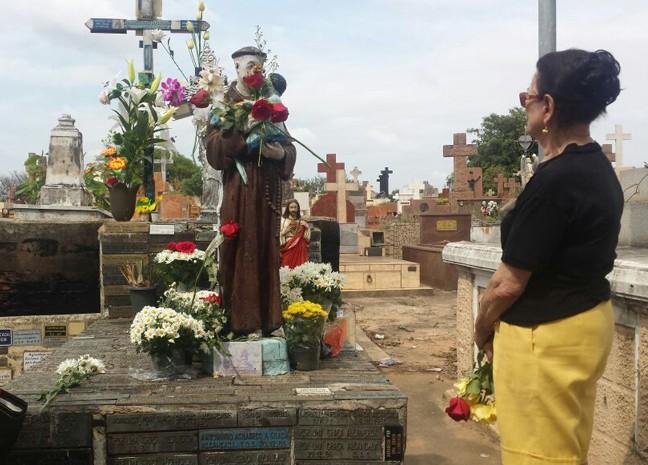 Lúcia prestando homenagem no túmulo de Toninho Escravo (Foto: Arlete Moraes/ G1)