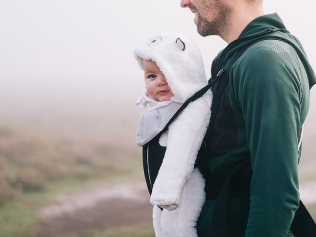 Pai caminha com seu filho preso ao peito. Projeto aprovado pelo Senado nesta quarta-feira (3) amplia de 5 para 20 dias a duração da licença-paternidade (Foto: Mint Images)
