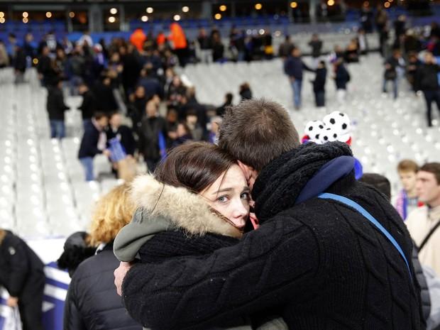Casal se abraça durante retirada do público após explosões ouvidas no Stade de France, em noite marcada por ataques terroristas simultâneos em Paris (Foto: Christophe Ena/AP)