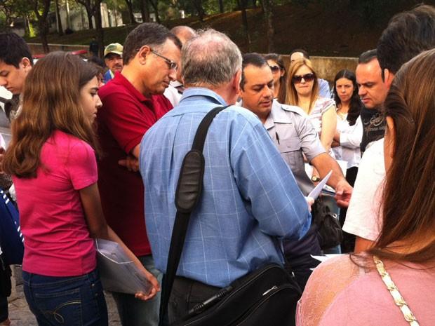 Solicitantes de visto cercam policial em frente ao Casv Alto de Pinheiros (Foto: Flávia Mantovani/G1)