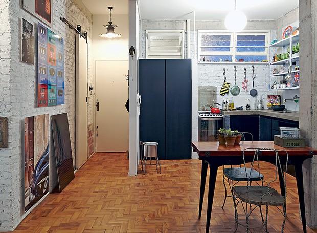 Como gosta de fugir do convencional, o fotógrafo Lufe Gomes colocou estantes de aço, típicas de escritório, na cozinha, que antes era fechada. Na reforma, ele aproveitou tacos retirados do apartamento vizinho. A porta preta esconde a lavanderia (Foto: Lufe Gomes e Victor Affaro/Casa e Jardim)