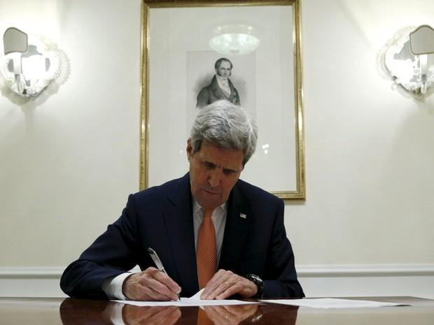 O secretário de Estado dos EUA, John Kerry, assina documentos que certificam que o Irã cumpriu sua parte no acordo nuclear e possibilitam a suspensão das sanções ao país, em Viena, no sábado (16) (Foto: Reuters/Kevin Lamarque)