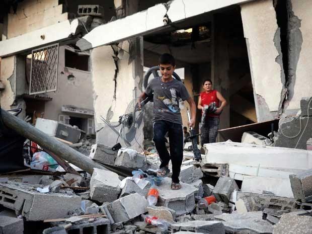 Meninos palestinos buscam pertences em uma casa danificada. (Foto: Finbarr O'Reilly / Reuters)