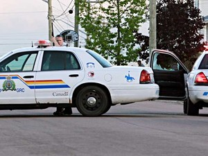 Policial armado protegido por seu carro, numa rua de Moncton. (Foto: Ron Ward / Moncton Times / Via Reuters)