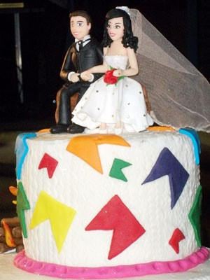 Os noivos foram presenteados com o bolo decorado, com os vestidos e ternos,  usados durante a cerimônia coletiva (Foto: Rafael Melo/G1)