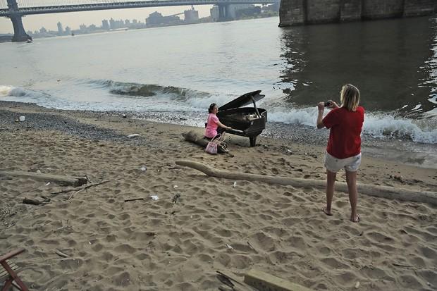 Curiosos tiraram fotos em piano colocado em praia em Nova York, nos EUA (Foto: Spencer Platt/Getty Images/AFP)