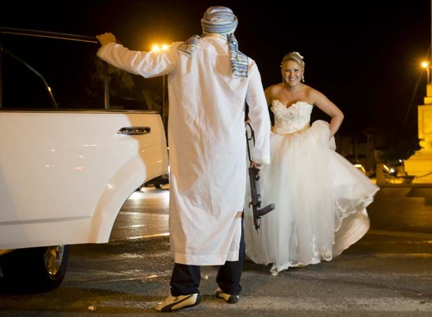 Homem abre a porta do carro para uma das noivas (Foto: Vadim Ghirda/AP)