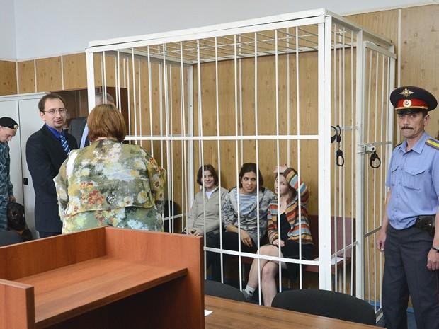 Atrás das grades, membros do grupo Pussy Riot participam de auditoria em tribunal russo (Foto: Natalia Kolesnikova/AFP)