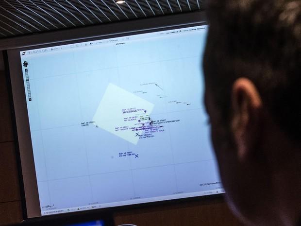 Oficial monitora barcos que fazem parte de resgate ao norte da Líbia (Foto: Angelo Carconi / ANSA via AP)