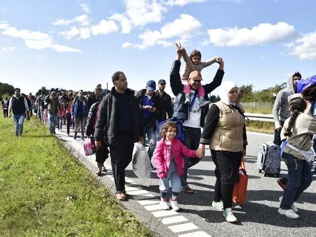 Imigrantes, a maioria da Siria, caminham nesta segunda-feira (7) em estrada na Dinamarca para buscar asilo na Suécia (Foto: AFP PHOTO / Scanpix Denmark /BAX LINDHARDT DENMARK OUT)