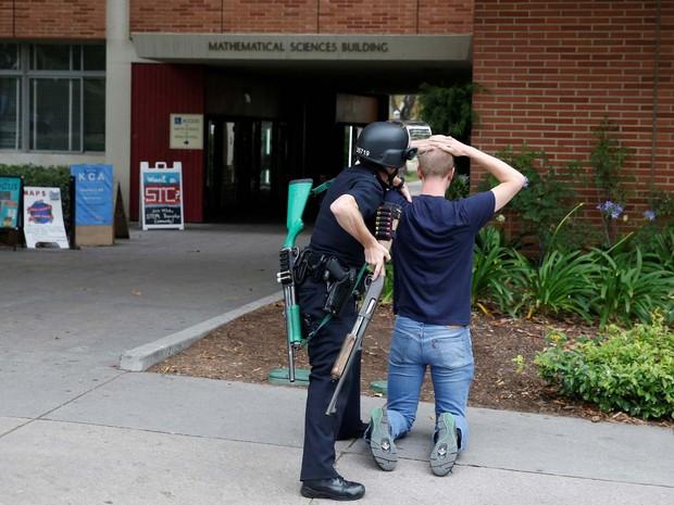 Policial revista estudante da Universidade da Califórina nesta quarta-feira (1º) durante busca por possível atirador no campus (Foto: REUTERS/Patrick T. Fallon)